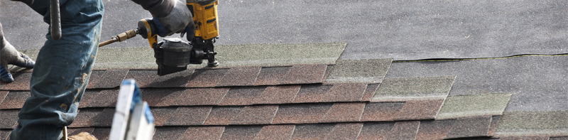 roofers installing a new roof on residential home. weatherlock material and brown asphalt roofing shingles