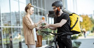 Photo of man delivering food to a woman.